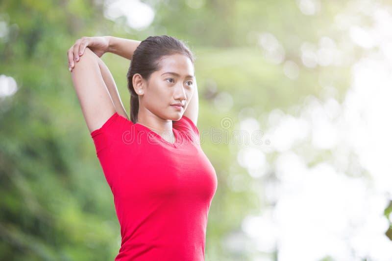 Asiatisk kvinna som gör sträcka övning under det utomhus- arga drevet royaltyfri foto