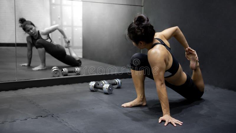 Asiatisk kvinna som g?r ?vning i konditionidrottshall royaltyfri fotografi