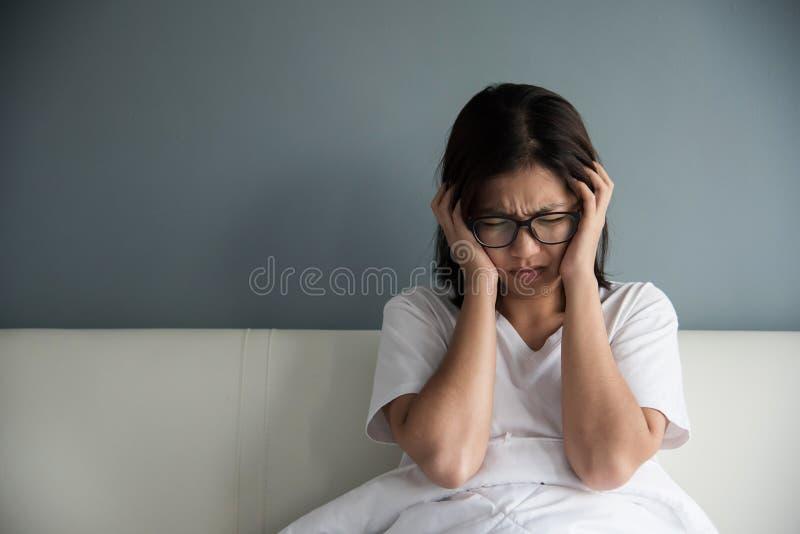 Asiatisk kvinna som har huvudvärk på hennes säng royaltyfria foton
