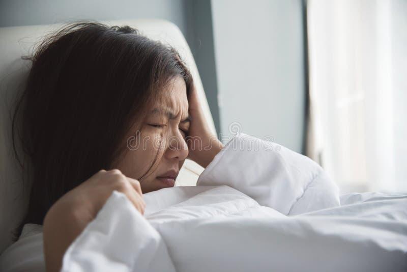 Asiatisk kvinna som har huvudvärk på hennes säng migrän Sjukdom disea arkivbilder