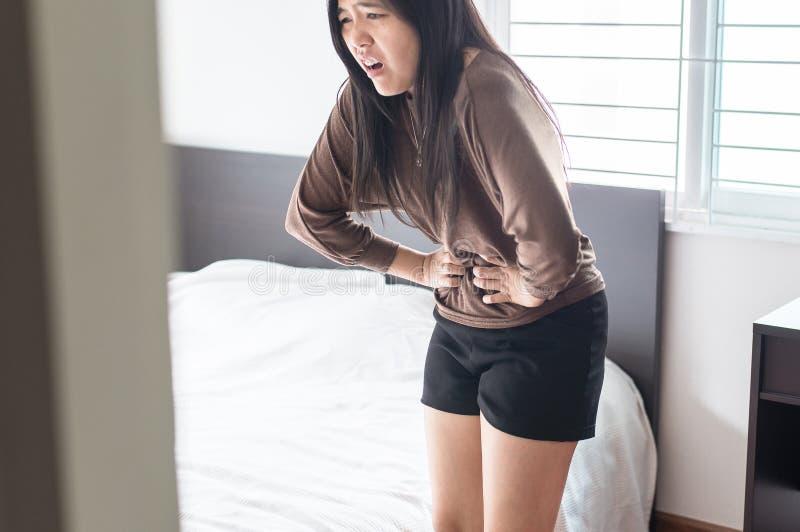 Asiatisk kvinna som har smärtsamt magknip i sovrum efter vak upp, kvinnliga periodkramper arkivfoton
