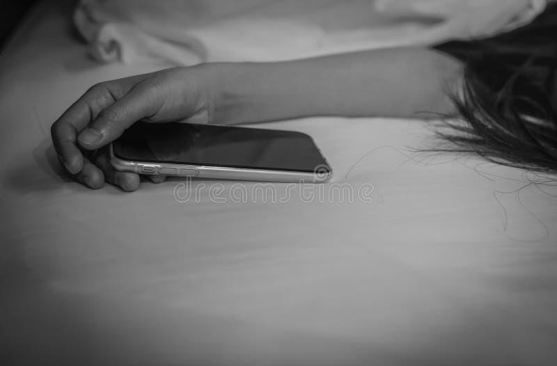 Asiatisk kvinna som hemma sover i säng och handinnehavmobiltelefon Kvinna som använder smartphonen i sovrum Missbrukat använda fö fotografering för bildbyråer