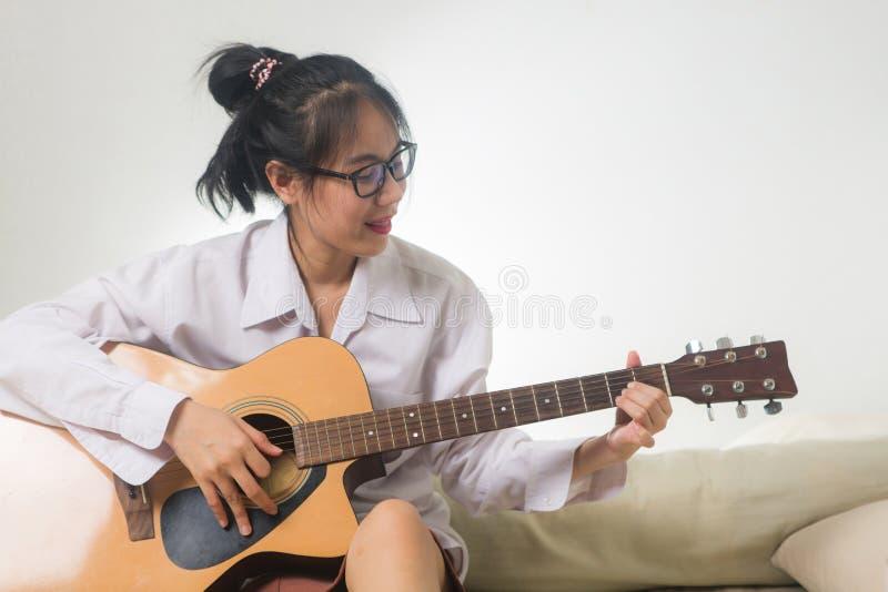 Asiatisk kvinna som hemma spelar gitarrsammanträde på säng med att le framsidan arkivfoto