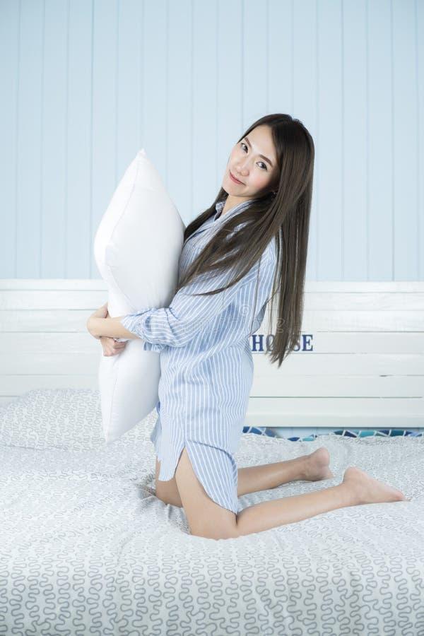Asiatisk kvinna som kramar kudden på sängen i hennes sovrum fotografering för bildbyråer