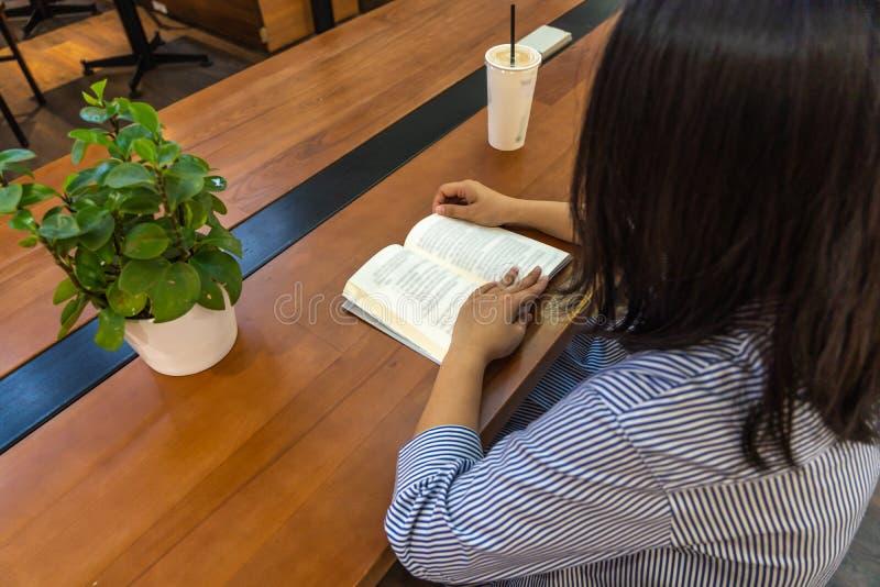 Asiatisk kvinna som läser en bok som på rymmer händer royaltyfria bilder