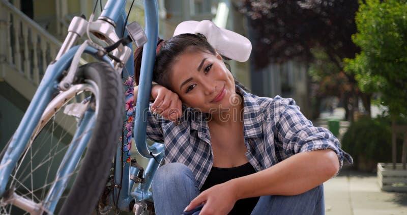 Asiatisk kvinna som ler med hennes cykel royaltyfri foto