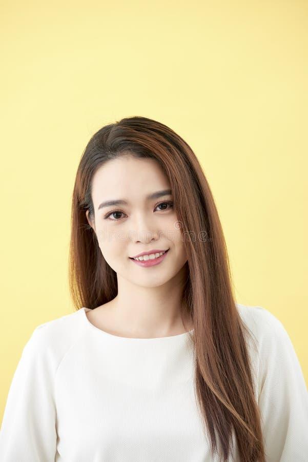 Asiatisk kvinna som ler med långa hårblåtiror för skrattgrop på härlig asiatisk flicka för gul för flickaframsida för bakgrund gu royaltyfria foton