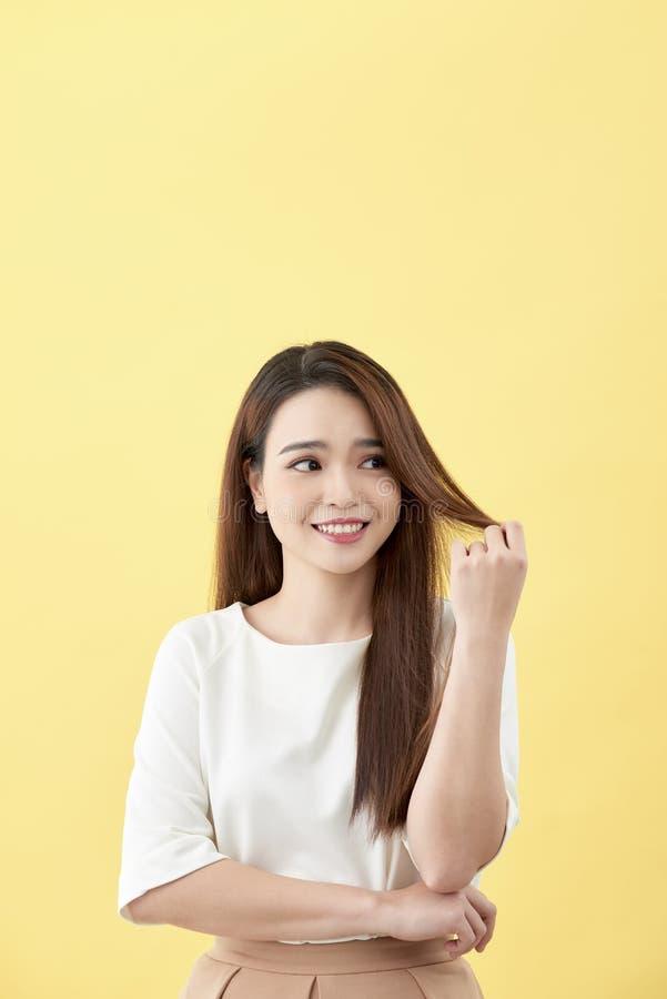 Asiatisk kvinna som ler med långa hårblåtiror för skrattgrop på härlig asiatisk flicka för gul för flickaframsida för bakgrund gu royaltyfri foto