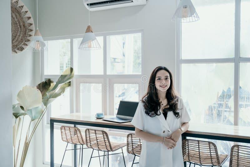 Asiatisk kvinna som ler, medan arbeta sig i kaf? royaltyfria bilder
