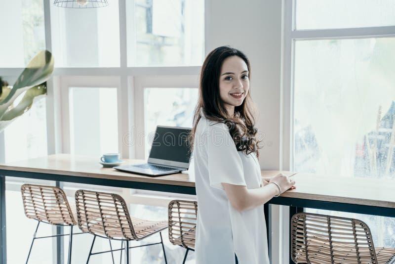 Asiatisk kvinna som ler, medan arbeta sig i kaf? royaltyfri foto