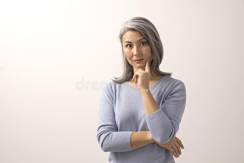 Asiatisk kvinna som ler och pekar hennes finger till hennes kind royaltyfria foton