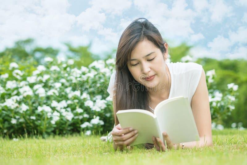 Asiatisk kvinna som ligger på gräsfältet för att läsa en vit bok i parkera royaltyfri foto