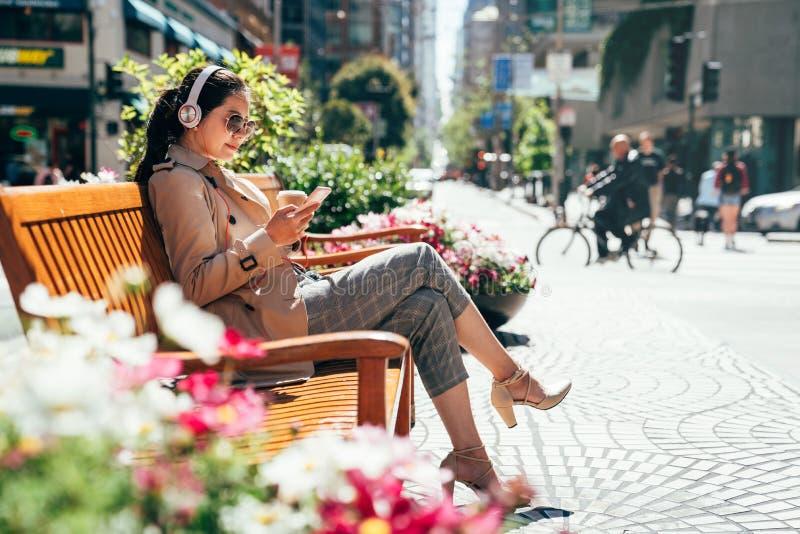 Asiatisk kvinna som lyssnar till musik som vilar på bänk royaltyfria bilder