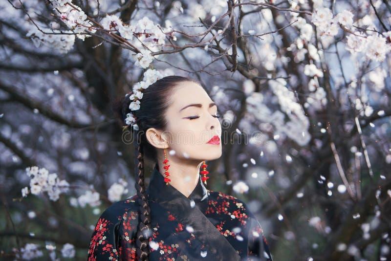 Asiatisk kvinna som mediterar i trädgård arkivfoto
