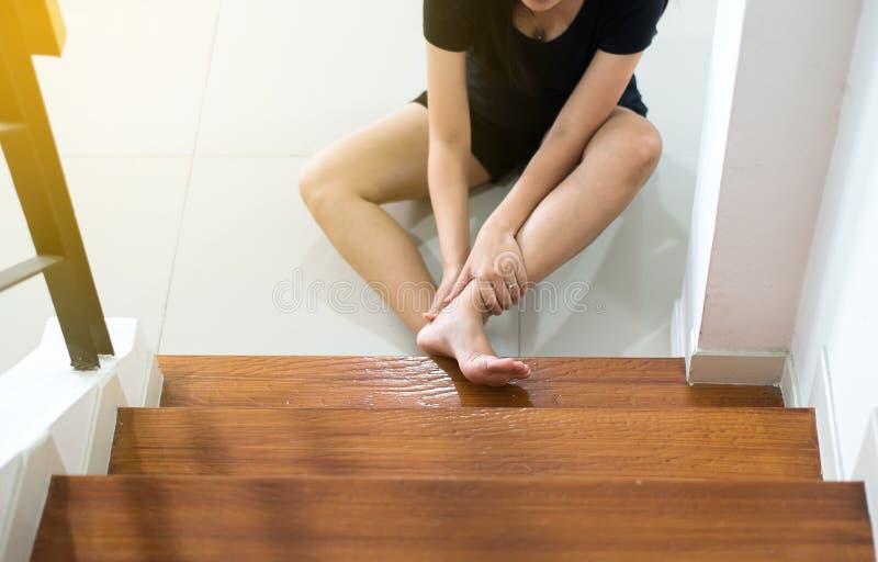 Asiatisk kvinna som ner faller av trappan, kvinnlig hand trycka på henne sårade ben royaltyfria foton