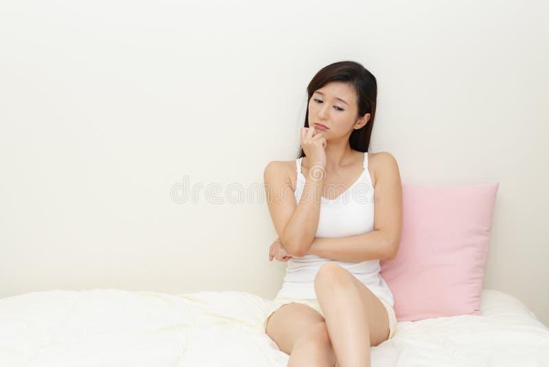 Asiatisk kvinna som oroas arkivbild