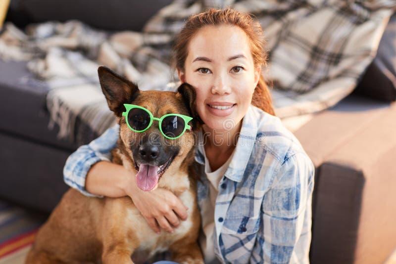 Asiatisk kvinna som poserar med den roliga hunden royaltyfria bilder