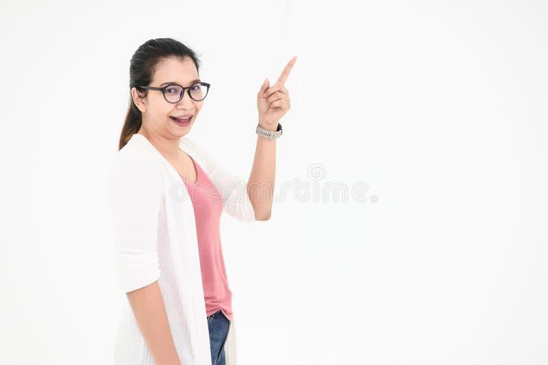 Asiatisk kvinna som poserar och pekar fingret på tomt utrymme med den tillfälligt dräkten och glasögon i lyckligt lynne på vit is fotografering för bildbyråer
