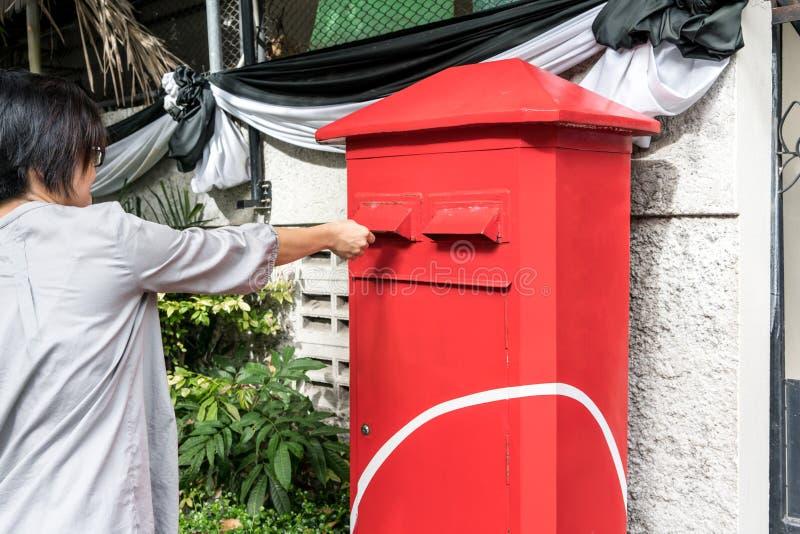 Asiatisk kvinna som postar en bokstav till den röda postboxen arkivfoton
