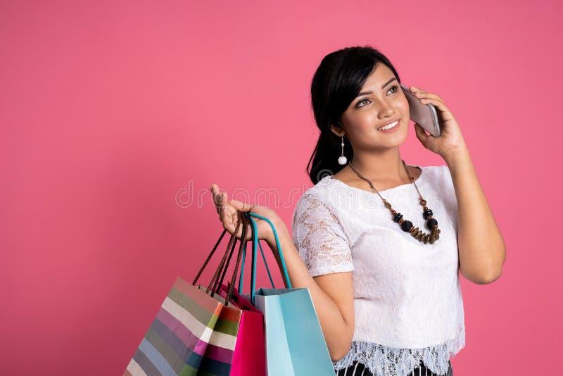 Asiatisk kvinna som rymmer den shoppingpåsar och telefonen arkivbild