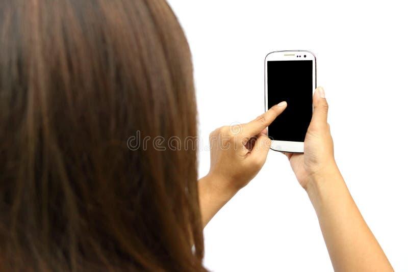 Asiatisk kvinna som rymmer den smarta telefonen i handen och bruksfingret som trycker på på den svarta skärmen på vit bakgrund arkivfoto