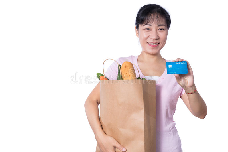 Asiatisk kvinna som rymmer en shoppingpåse full av livsmedel och kreditering royaltyfria bilder