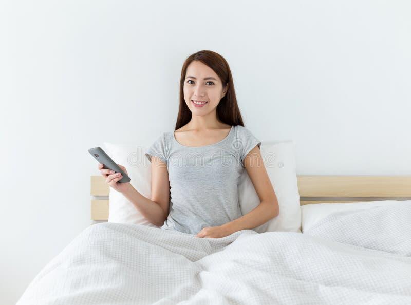 Asiatisk kvinna som rymmer mobiltelefonen och sitter på sängen royaltyfri foto