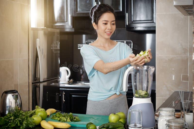 Asiatisk kvinna som sätter frukter i blandare arkivfoton