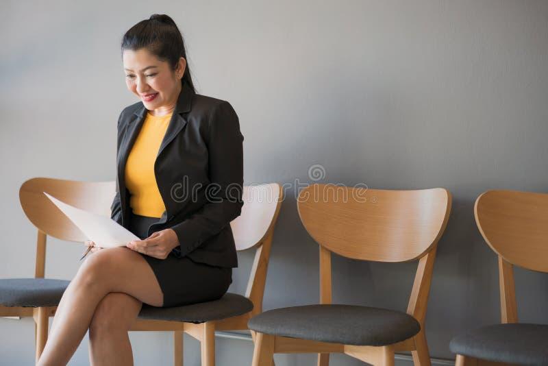 Asiatisk kvinna som sitter i en stol som läser ett dokument med säkert, medan vänta på en jobbintervju arkivfoton