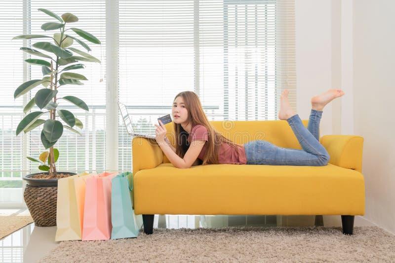 Asiatisk kvinna som sitter p? den gula soffan genom att anv?nda b?rbar dator- och craditkortet som direktanslutet shoppar n?ra f? arkivfoton