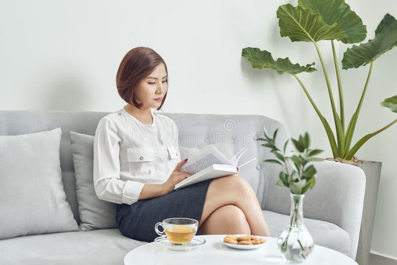 Asiatisk kvinna som sitter på soffan och dricker te medan läsebok i vardagsrum royaltyfria bilder