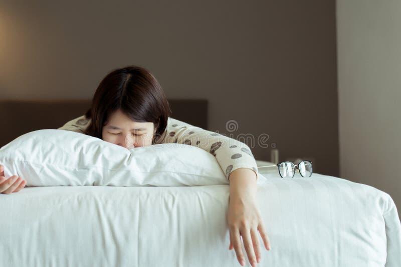 Asiatisk kvinna som sover lögn på magen på säng, bra dröm, dagdröm, lycklig tid arkivbild