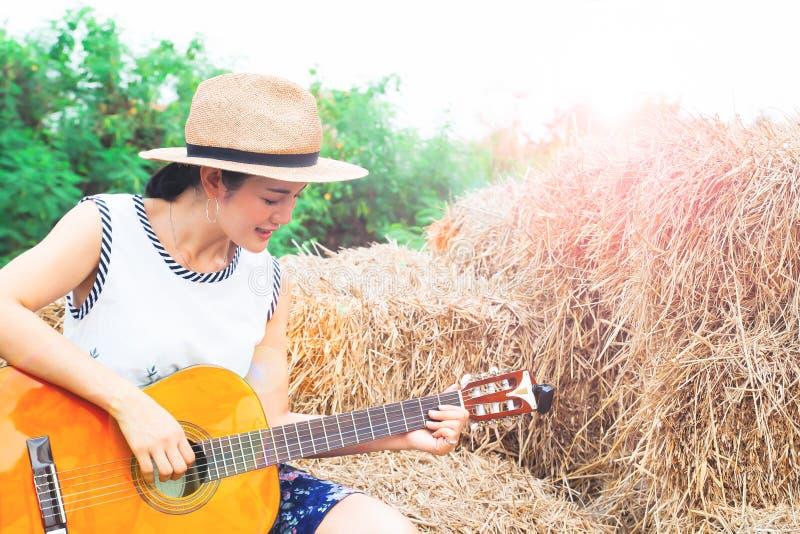 Asiatisk kvinna som spelar gitarren som sitter på sugrör lycklig kvinna royaltyfri fotografi