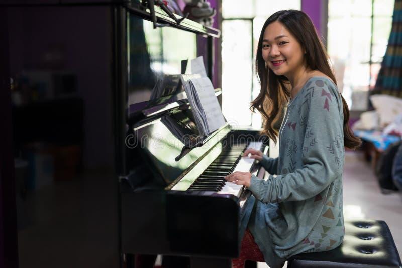 Asiatisk kvinna som spelar pianot i hus arkivfoton