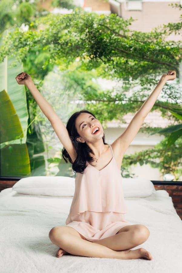 Asiatisk kvinna som sträcker sammanträde på säng i morgonen royaltyfri foto