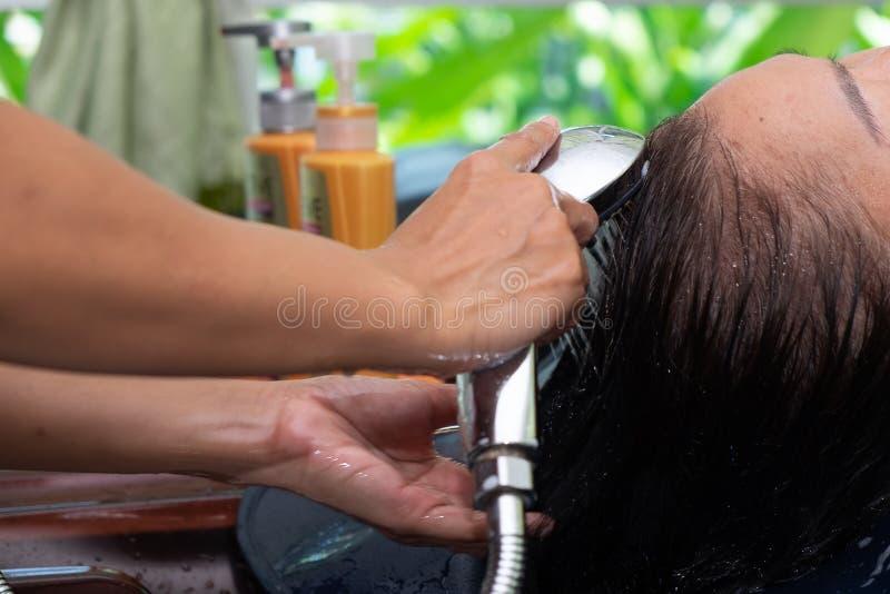 Asiatisk kvinna som torkar kundhår med schampo i frisören Beauty Salon fotografering för bildbyråer
