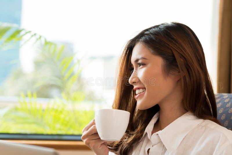 Asiatisk kvinna som tycker om doftande kaffe royaltyfria bilder