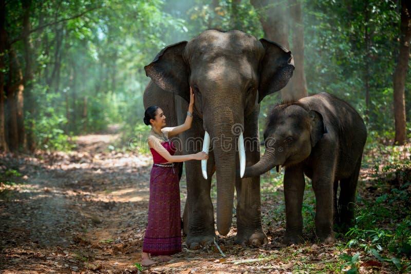 Asiatisk kvinna som tycker om med elefanten och sonen på Chang Village arkivfoton