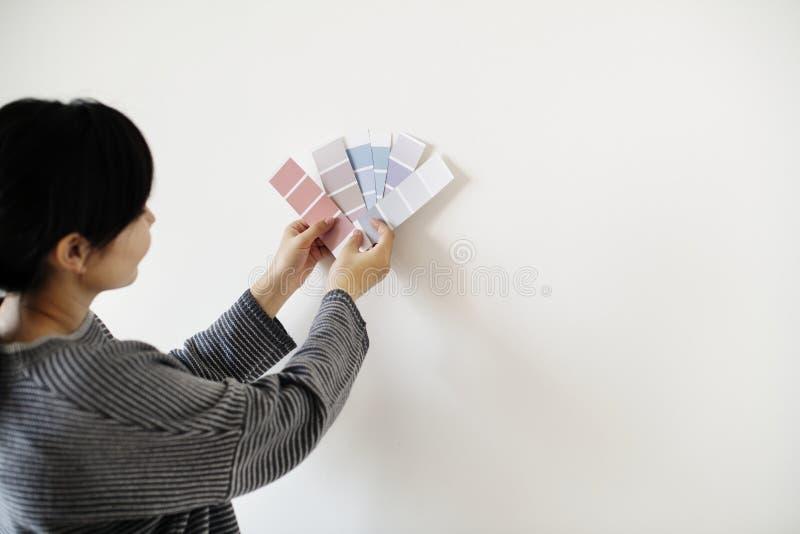 Asiatisk kvinna som väljer väggfärg arkivbilder