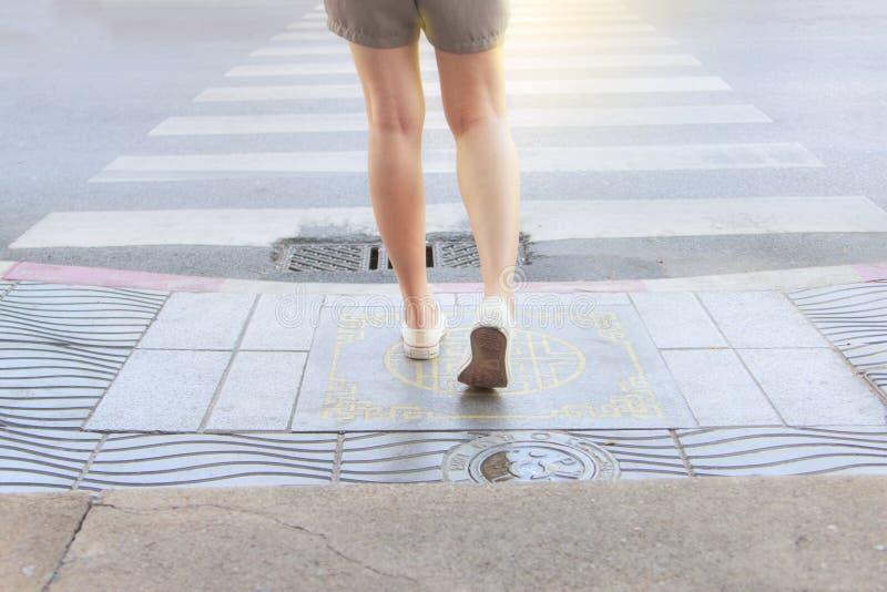 Asiatisk kvinna som väntar på vandringsledtrottoaren som korsar gatan bara Vänta på trafikljus på övergångsstället royaltyfria bilder