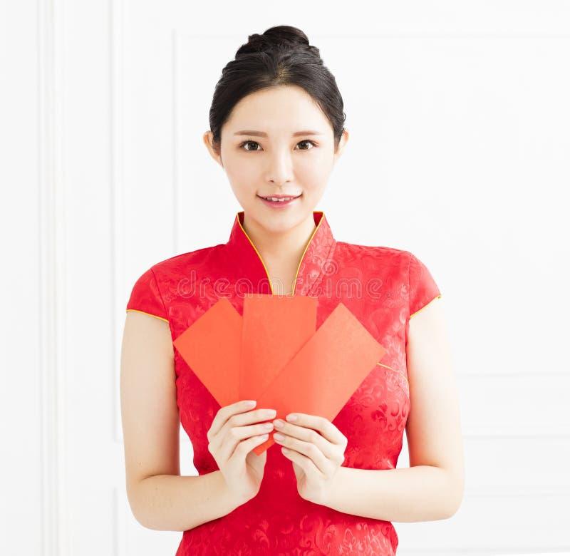Asiatisk kvinna som visar det röda kuvertet fotografering för bildbyråer