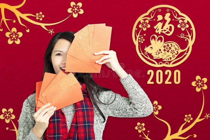 Asiatisk kvinna som visar röda kuvert för kineserna nytt år Kinesisk text - nytt år 2020 royaltyfri bild