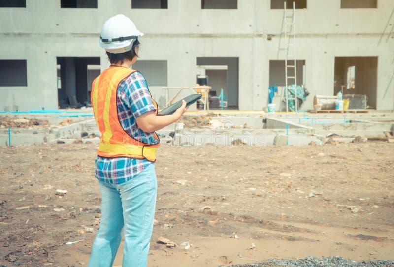 Asiatisk kvinnaarbetare och tekniker på byggnadsplats genom att använda minnestavlan för att kontrollera exaktheten som är bitvis royaltyfria bilder