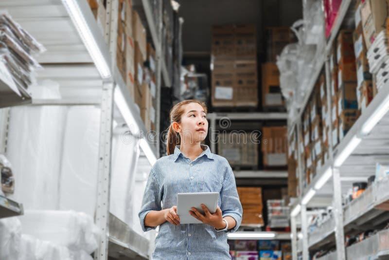 Asiatisk kvinnaarbetare som arbetar med kontrollerande askar logistiska import- för digital minnestavla och exporttillförselpacka royaltyfria foton