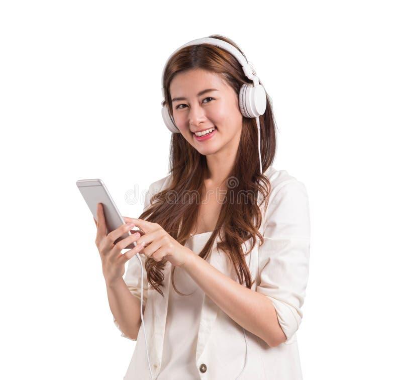Asiatisk kvinnabruksmobil för lyssnande musik arkivfoto