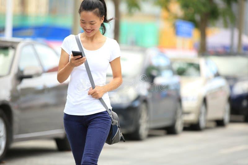 Asiatisk kvinnabrukssmartphone royaltyfria foton