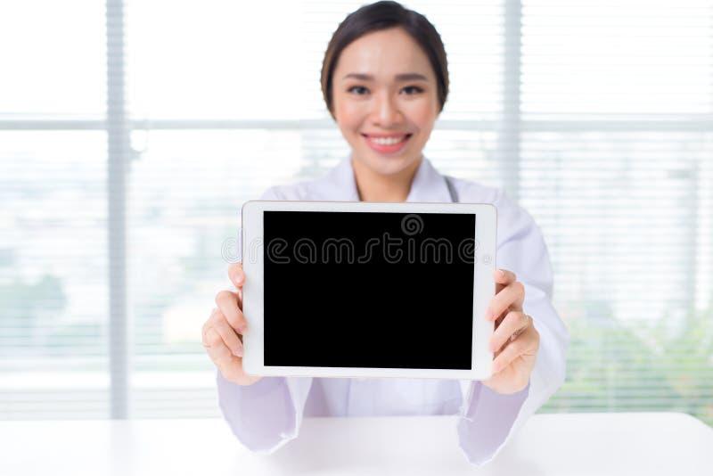 Asiatisk kvinnadoktor som visar den digitala minnestavlaskärmen royaltyfria bilder