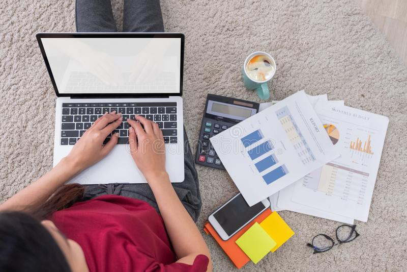 Asiatisk kvinnafrilans för bästa sikt som arbetar på bärbara datorn med skrivbordsarbete royaltyfri foto