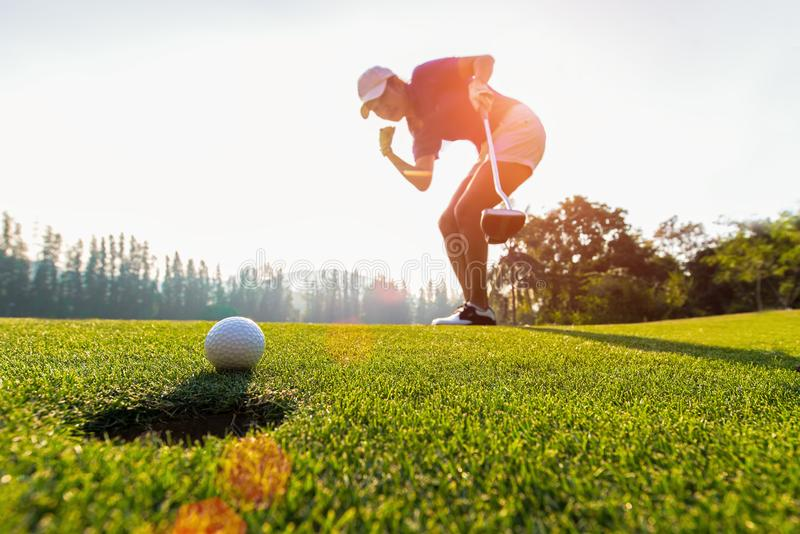Asiatisk kvinnagolfarehandling att segra, efter lång sättande golfboll på den gröna golfen, solnedgångtid, arkivbilder