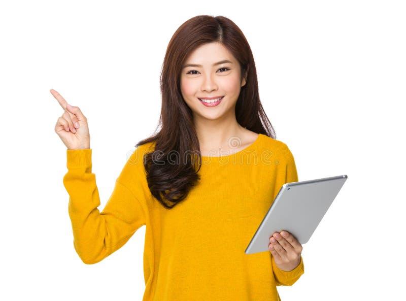 Asiatisk kvinnahåll med den digitala minnestavlan och fingret som uppåt pekar royaltyfria bilder